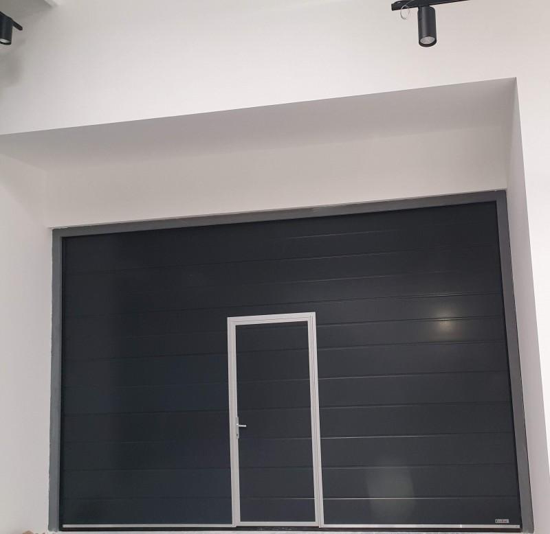 DITEC iparikapu Automatizált ipari garázskapu telepítésünk antracit színű, személyi ajtós kivitelben Bp 12. kerületi design bemutatóterembe